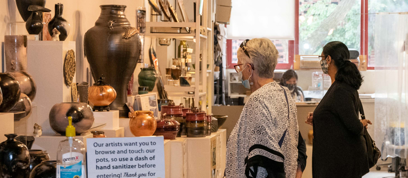 Visitors wearing masks in ceramics studio